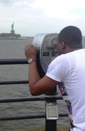 Kolowale looking through binoculars at the Statue